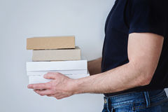 Man holding three boxes. A strong man in jeans and black t-shirt is holding three boxes in his hands Stock Photo