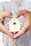 Man holding tiny wooden house Royalty Free Stock Image