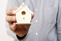 Man holding tiny wooden house Royalty Free Stock Images