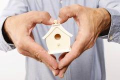Man holding tiny wooden house Stock Photo