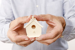 Man holding tiny wooden house Stock Images