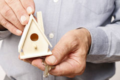 Man holding tiny wooden house Royalty Free Stock Photography