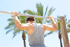Man holding on to pull up bar Stock Images