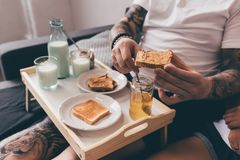 Man holding toast with peanut butter. Partial view of tattooed man holding toast with peanut butter while having breakfast in bed Stock Photography