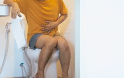 Man holding toilet paper and using toilet with suffering from Diarrhea and Hemorrhoids after wake up in morning at home royalty free stock images