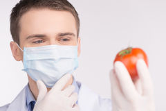 Man holding tomato and wearing mask. Stock Photos