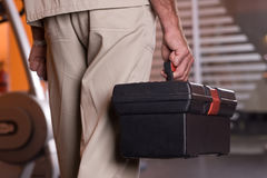 Man holding tool box. Man in uniform is standing and holding tool box Stock Photography