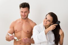Man holding tooth brush and her wife combing her hair Royalty Free Stock Image