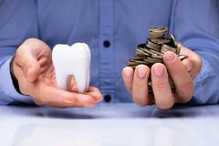 Man Holding Tooth And Golden Coins royalty free stock image