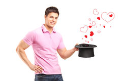 Man holding a top hat and hearts coming out Stock Images