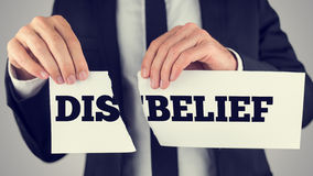 Man holding torn paper with the words Dis-Belief. Man holding a torn paper sign in his hands with the words - Dis - Belief - spread over the two halves depicting Stock Photography