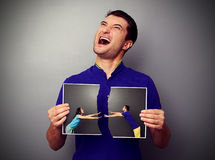 Man holding the torn photo with couple. And gibing over dark background stock photography