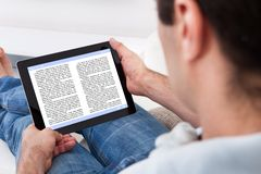 Man holding touch screen device showing an e-book Royalty Free Stock Photo