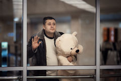 Man holding toy bear and looking sadly into the distance. Royalty Free Stock Photo