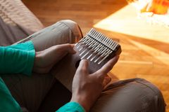 Man holding traditional African musical instrument kalimba in one`s hands. Man playing on a plucked instrument kalimba. Royalty Free Stock Image