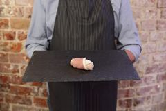 Man holding tray with pig in blanket on sausage and bacon stock images