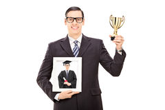 Man holding trophy and picture of his graduation Royalty Free Stock Photos
