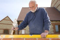 Man holding trowel and using level tool on brick wall Royalty Free Stock Images