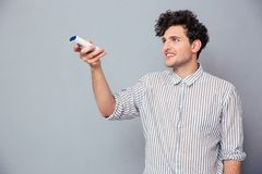 Man holding TV remote Stock Photos