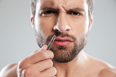 Man holding tweezer and frowning Stock Photography