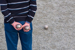 Man holding two balls behind his back playing petanque Royalty Free Stock Images