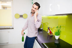 Man holding two beers and calling his friends Stock Photography