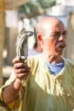 Man holding two desert monitors  in Tozeur Zoo. TOZEUR, TUNISIA - SEPTEMBER 16 : A man holding two desert monitors on September 16th, 2012 in Zoo in Tozeur Royalty Free Stock Image