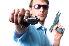 Man holding two guns in blue shirt. Young men with airsoft guns against white background stock photography