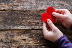 Man holding two halves of a broken heart. On the wooden background royalty free stock photos
