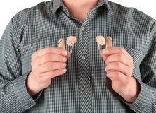 Man holding two hearing aids.  Stock Photo