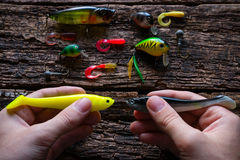 Man holding two lures for fishing with spinning on table Stock Photo