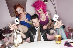 Man holding two playing cards with erotic females sitting besides him Stock Image