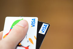 Man holding two Visa cards. MAY 4, 2015: A hand with bank credit cards visa stock image