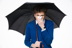 Man holding umbrella and blowing nose. Sick business man holding umbrella and blowing nose Royalty Free Stock Photo