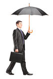 Man holding an umbrella and briefcase Royalty Free Stock Photo