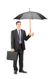 Man holding an umbrella and a briefcase Royalty Free Stock Photography