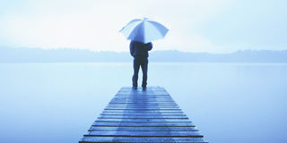 Man Holding an Umbrella on a Jetty by Tranquil Lake Concept Stock Photography