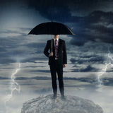 Man holding umbrella standing on the rock with bad weather Stock Photo