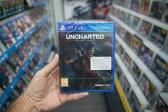 Man holding Uncharted The lost legacy videogame on Sony Playstation 4 console in store. Bratislava, Slovakia, october 2 2017: Man holding Uncharted The lost Royalty Free Stock Photography