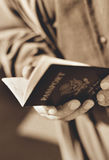 Man Holding a United States Passport. Photograph of a man holding a United States Passport in black and white with a sepia tone stock images