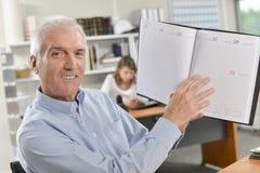 Man holding up agenda Stock Photo