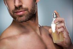 Man holding up bottle of perfume royalty free stock photo