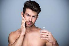 Man holding up bottle of perfume stock photos