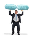 Man holding up giant pills saying HEALTH CARE Royalty Free Stock Photos