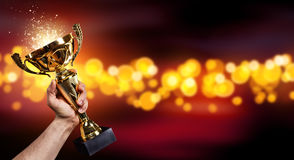 Man holding up a gold trophy cup. With abstract shiny background, copy space for text stock photo