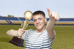 Man holding up a gold trophy cup as a winner. In a competition royalty free stock image