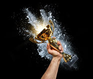 Man holding up a gold trophy cup. With powder explosion on background. Concept of success and achievement. on black background stock photos