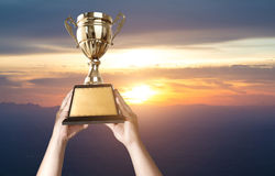 a man holding up a gold trophy cup with sunset sky background co stock image