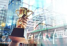 Man holding up a gold trophy cup,win concept. stock images