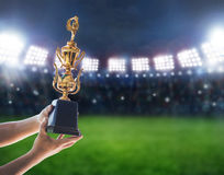 Man holding up a a gold trophy cup,win concept. Win concept,Man holding up a a gold trophy cup is winner in a competition in night stadium royalty free stock photos